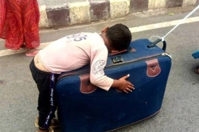Migrant mother carries her son as he sleeps on her suitcase - viral video